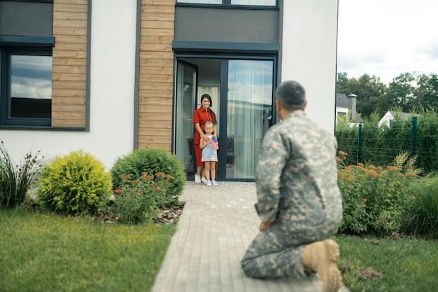 Vrouw en dochter. vrouw en dochter voelen zich gelukkig als ze kijken naar de militaire dienaar die eindelijk thuiskomt
