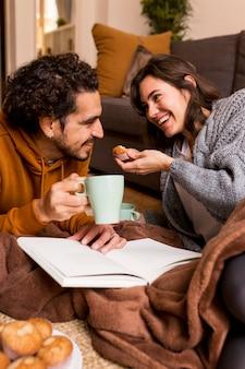 Vrouw en echtgenoot brengen samen tijd door binnen in een hygge-omgeving