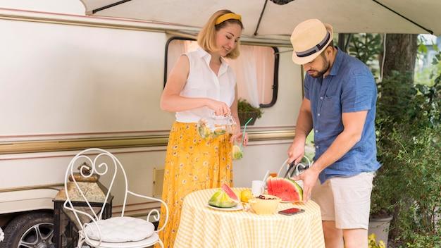Vrouw en echtgenoot die een watermeloen snijden