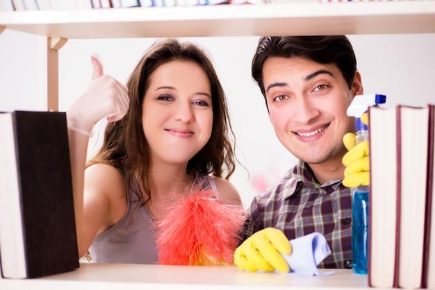 Vrouw en echtgenoot die stof van boekenrek schoonmaken