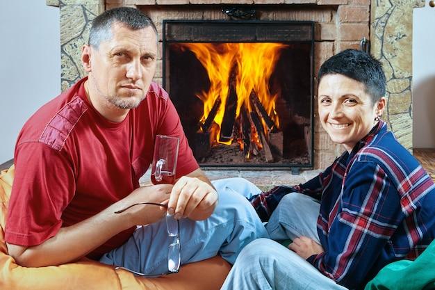 Vrouw en echtgenoot drinken wijn op zitzakken tijdens het vieren.
