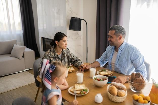 Vrouw en echtgenoot. militaire vrouw die de hand van de man aanraakt tijdens het ontbijt met het gezin