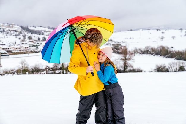 Vrouw en een dochter blij en omarmd met een veelkleurige paraplu in de sneeuw op een berg