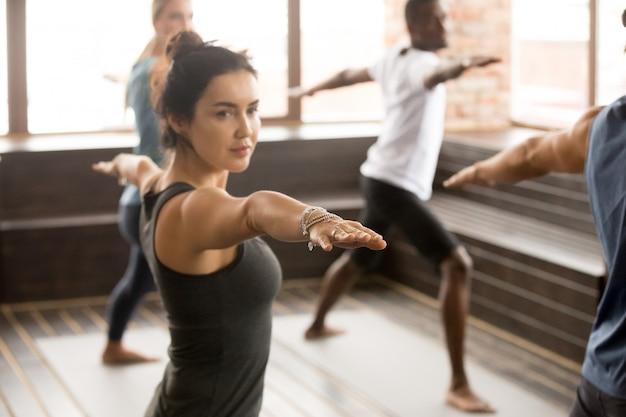 Vrouw en een groep sportieve mensen in warrior twee