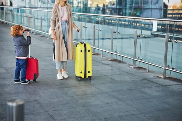 Vrouw en een jongen staan met bagage