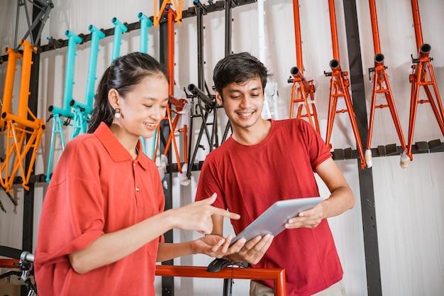 Vrouw en een man die digitale tablet gebruiken in een fietsenwinkel