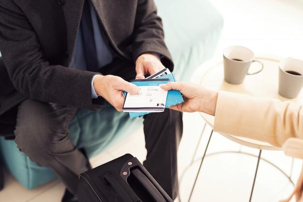 Vrouw en een man houden kaartjes voor het vliegtuig.