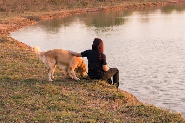 Vrouw en gouden hond op rivieroever