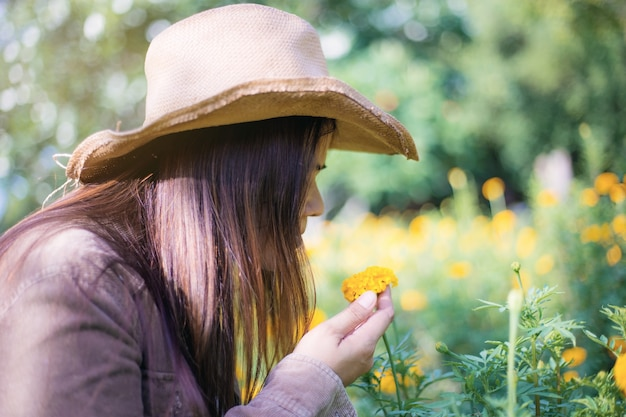 Vrouw en goudsbloembloem in tuin.