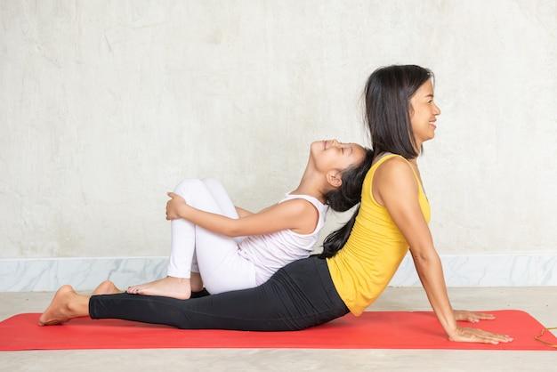 Vrouw en haar charmante kleine dochter die yoga doen