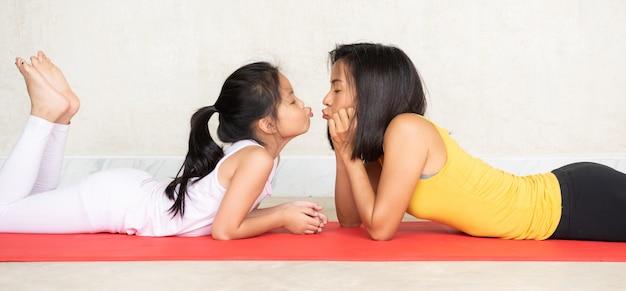 Vrouw en haar charmante kleine dochter op yogamat