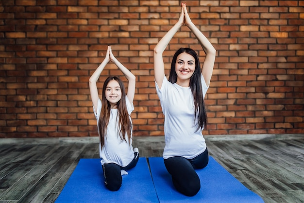 Vrouw en haar dochter beoefenen thuis yoga en meditatie, liggen op de grond en doen de pose.