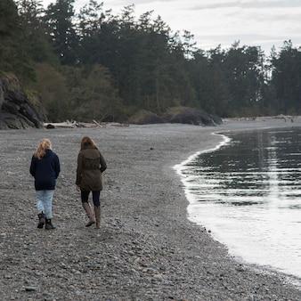 Vrouw en haar dochter die bij de oever van het meer, het park van de staat van de deceptionpas, eiken haven, washington st lopen