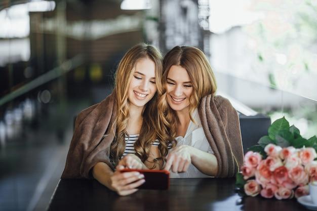 Vrouw en haar dochter met behulp van een smartphone