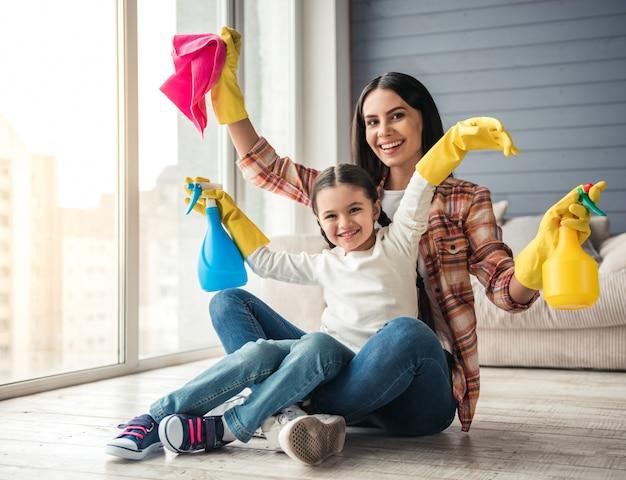 Vrouw en haar dochter zitten op de vloer. schoonmaak concept