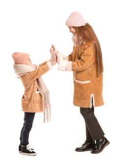 Vrouw en haar dochtertje in winterkleren op witte ondergrond