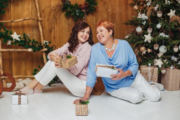 Vrouw en haar hogere moeder die dichtbij kerstmisboom glimlachen