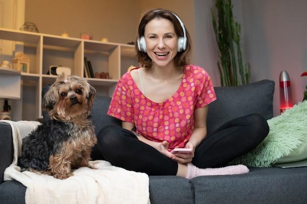 Vrouw en haar hond die met hoofdtelefoon een muziek luisteren
