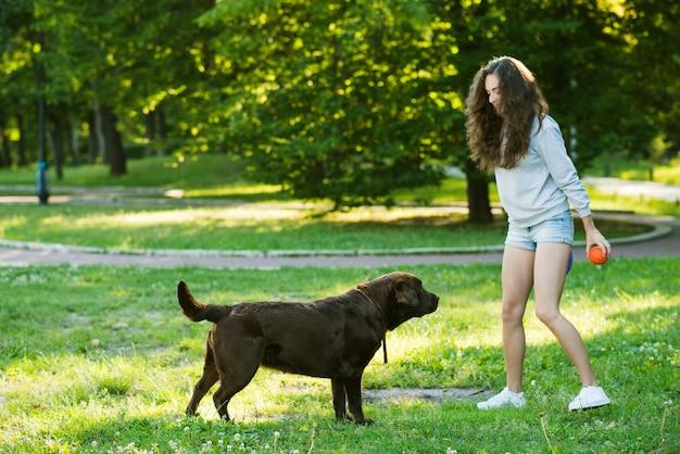 Vrouw en haar hond die op gras spelen