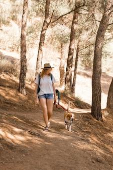 Vrouw en haar hond wandelen in het bos