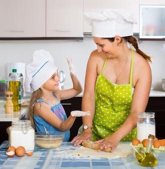 Vrouw en haar kleine assistent kneden pasta