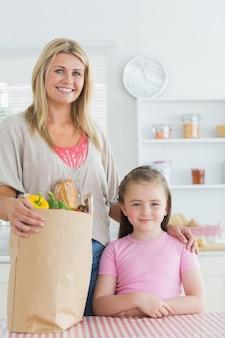 Vrouw en haar meisje die bij de keuken glimlachen