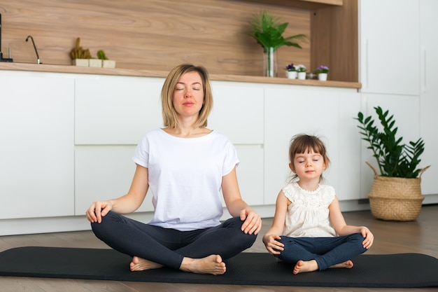 Vrouw en haar schattige dochtertje zitten in een lotushouding terwijl ze thuis samen yoga doen