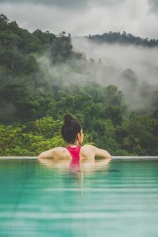 Vrouw en het zwembad kijken naar de scène voor het mistige bos
