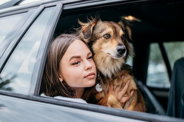 Vrouw en hond die door autoraam kijken