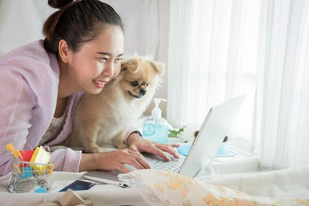 Vrouw en hond tonen van geluk na online winkelen met de levensstijl new normal voor zelfquarantaine tijdens de uitbraak van de corona-virusziekte (covid-19).