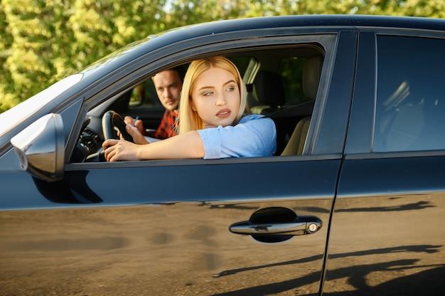 Vrouw en instructeur kijken uit het autoraam, rijschool. man die dame leert voertuig te besturen. rijbewijs opleiding