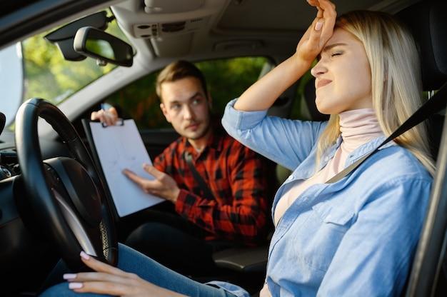 Vrouw en instructeur met checklist in auto, rijschool. man die dame leert voertuig te besturen. rijbewijs opleiding