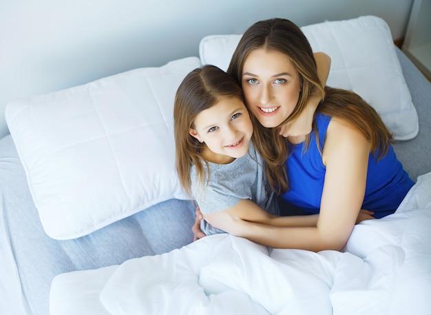 Vrouw en jong meisje die in bed het glimlachen liggen