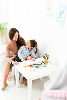 Vrouw en jong meisje die zich bij bureau verenigen