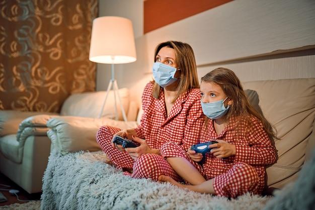Vrouw en jong meisje dragen pyjama's en medische beschermende maskers zittend op de bank in de woonkamer met videogamecontrollers thuis isolatie auto quarantaine, covid-19
