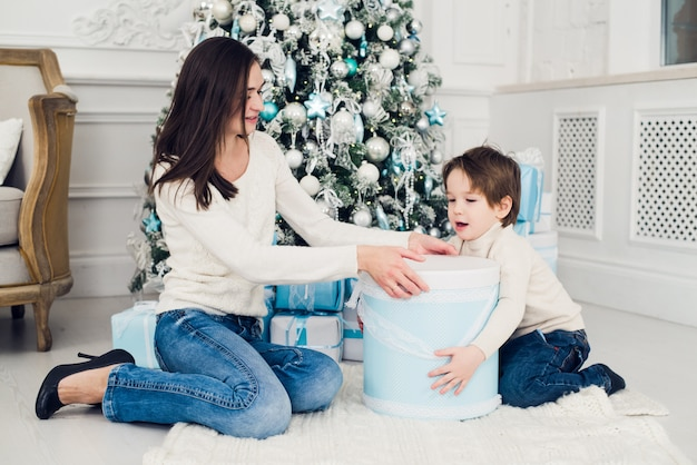 Vrouw en jongen die kerstcadeaus controleren