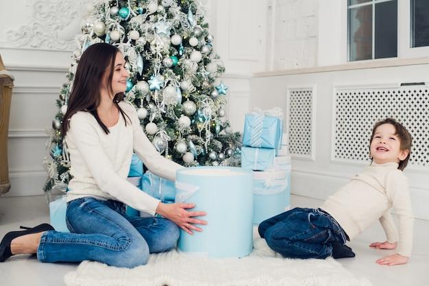 Vrouw en jongen die kerstcadeautjes thuis controleren