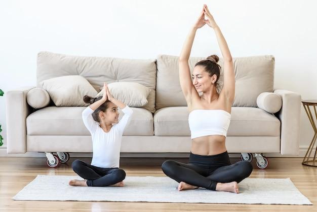 Vrouw en kind beoefenen yoga thuis samen op tapijt in de woonkamer