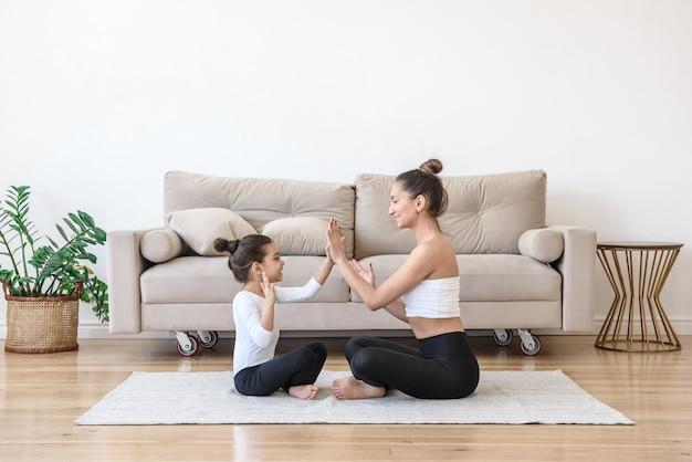 Vrouw en kind brengen thuis in de woonkamer speels tijd samen door