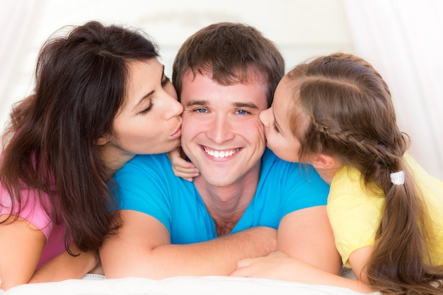 Vrouw en kind die je vader kussen. gelukkig gezin plezier thuis fun