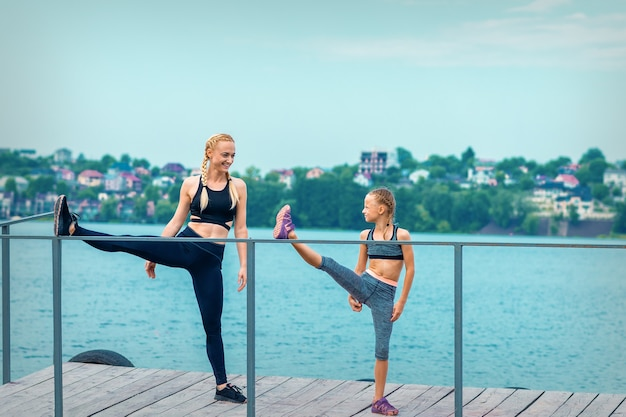 Vrouw en kind doen sportoefeningen die hun benen strekken op de pier van het meer