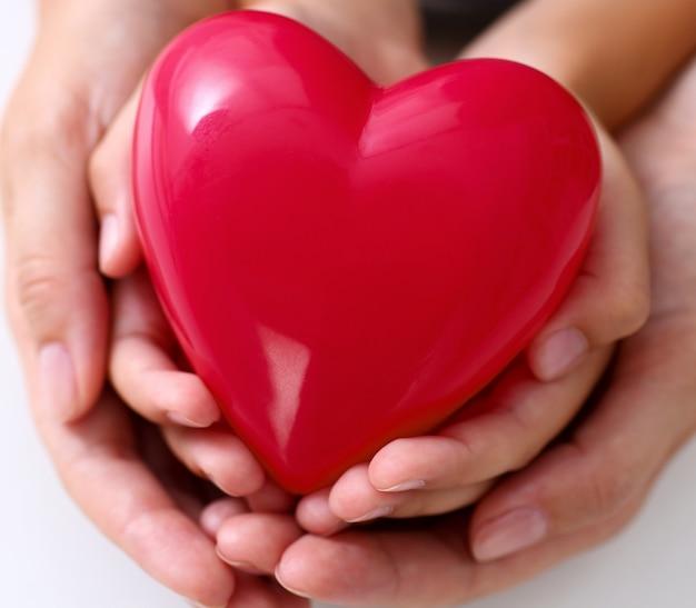 Vrouw en kind houden rode speelgoed hart in armen