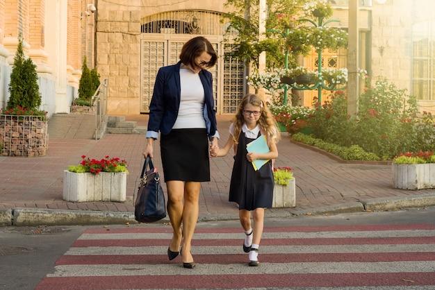 Vrouw en kind jonge schoolmeisje hand in hand, bij zebrapad