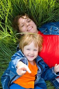 Vrouw en kind liggen op groen gras. gelukkig gezin
