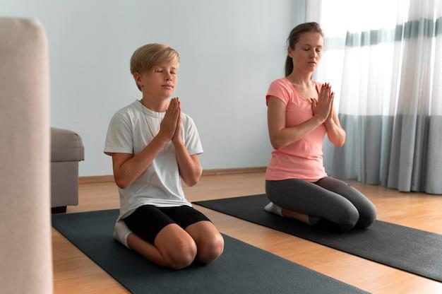 Vrouw en kind mediteren volledig shot