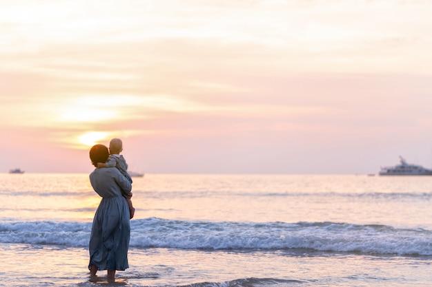 Vrouw en kind meisje staan in de zee in blauwe jurken en genieten van de zonsondergang. familie kalm.