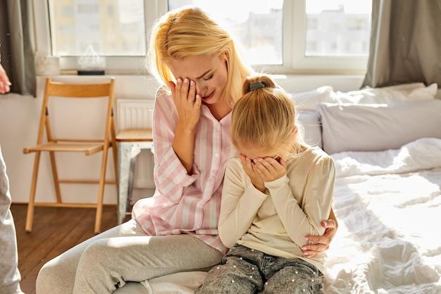 Vrouw en kind meisje zitten die lijden aan wreedheid van vader, concept van gewelddadige relaties, man schreeuwt en straft familieleden