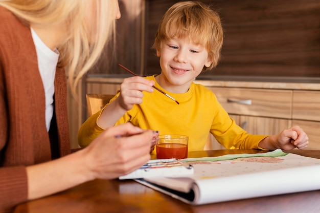Vrouw en kind met behulp van aquarellen close-up