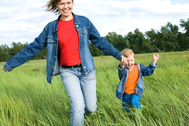 Vrouw en kind rennen op het veld. gelukkig gezin