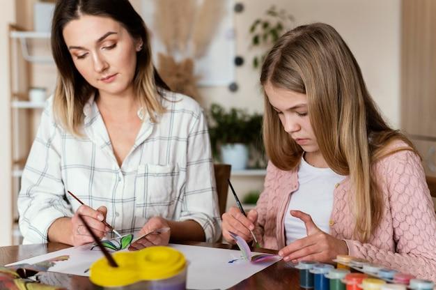 Vrouw en kind schilderen vlinders